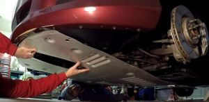 Lifting the Front Under Tray into place on an Aston Martin DB9